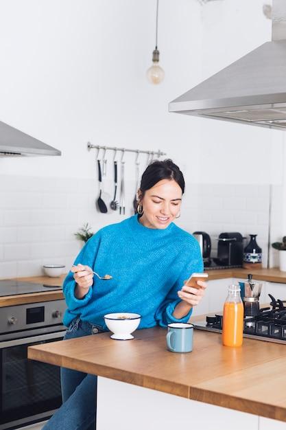 Donna moderna facendo colazione in cucina | Foto Gratis