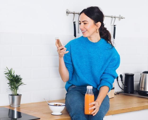 Donna moderna facendo colazione in cucina | Scaricare foto gratis
