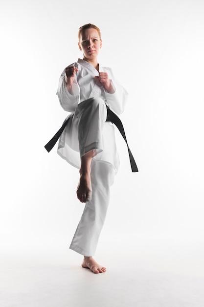 Donna motivata di karatè che dà dei calci alla vista frontale Foto Gratuite