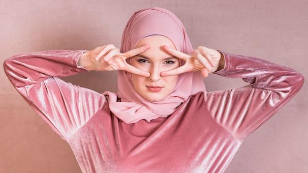 Donna musulmana arrabbiata che mostra il segno di v vicino ai suoi occhi sopra la superficie colorata Foto Gratuite