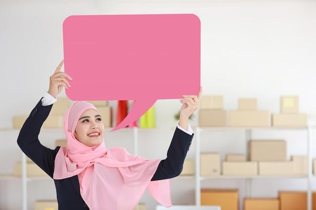 Donna musulmana asiatica attiva in vestito blu che sta e che tiene fumetto rosa Foto Premium