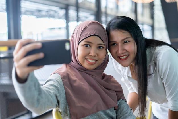 Donna musulmana che tiene smartphone e utilizzando la fotocamera anteriore per selfie scatto con amico Foto Premium
