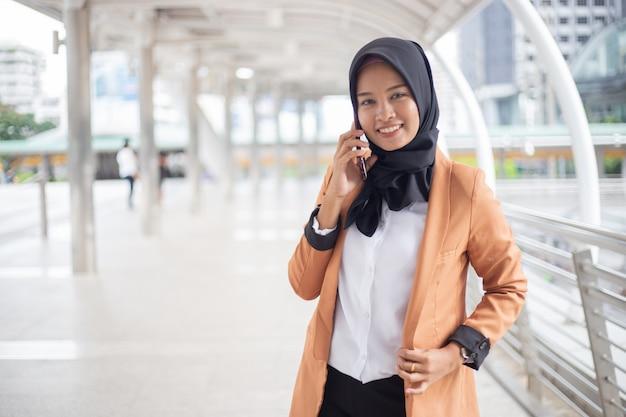 Donna musulmana di affari che utilizza telefono nella città. Foto Premium