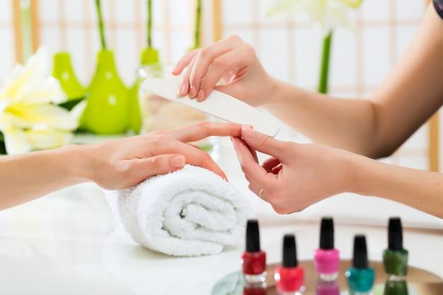 Donna nel salone del chiodo che riceve manicure Foto Premium