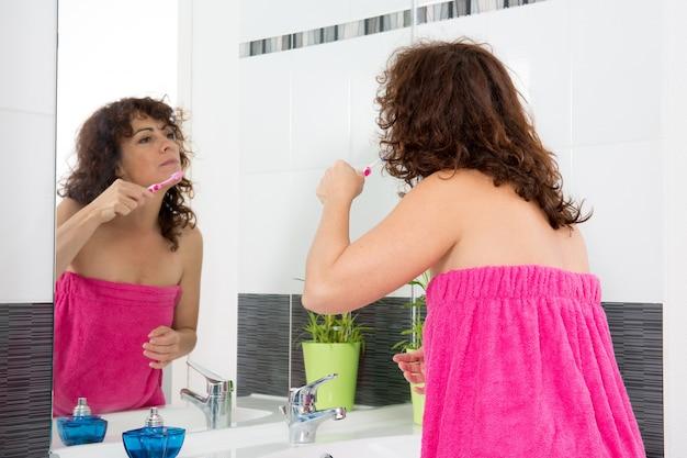 Donna nel suo bagno lavarsi i denti Foto Premium