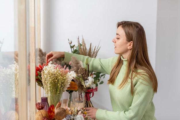 Donna nel suo negozio di fiori e fiori Foto Gratuite