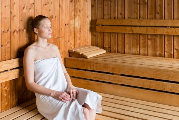 Donna nella stazione termale di benessere che gode della sauna Foto Premium