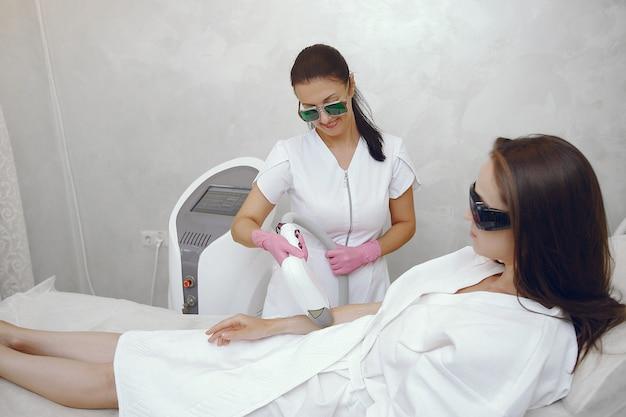 Donna nello studio di cosmetologia sulla depilazione laser Foto Gratuite