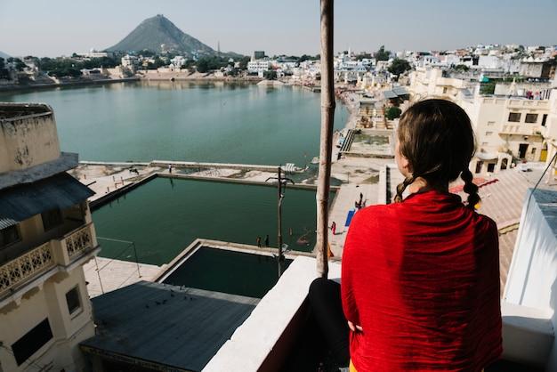Donna occidentale che gode di una vista del lago pushkar nel rajasthan Foto Gratuite