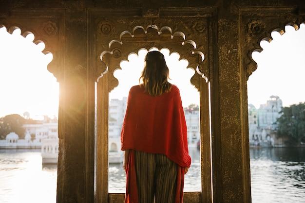 Donna occidentale che sta su un'architettura culturale in udaipur, india Foto Gratuite