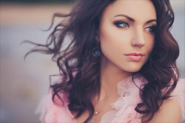 Donna pacifica di paradiso di vacanza che cammina sulla spiaggia dell'oceano di tramonto. ritratto del primo piano della ragazza in vestito romantico rosa Foto Premium