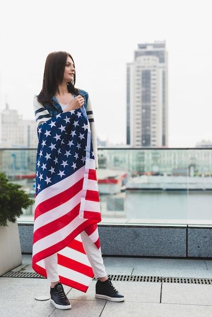 Donna patriottica avvolta in una grande bandiera a stelle Foto Gratuite