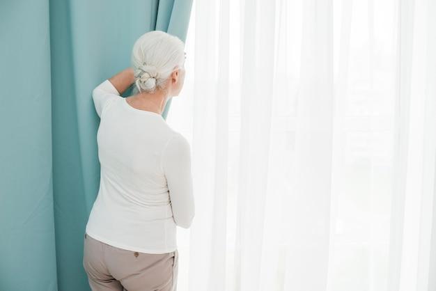 Donna più anziana che guarda attraverso la finestra Foto Gratuite