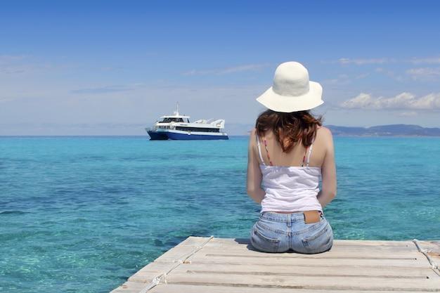 Donna posteriore turistica che osserva il mare del turchese di formentera Foto Premium