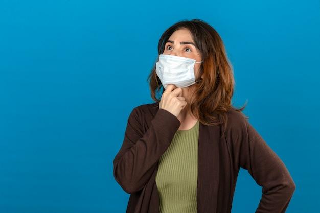 Donna premurosa che indossa cardigan marrone nella maschera protettiva medica che sta con la mano sul mento che cerca pensante sopra la parete blu isolata Foto Gratuite