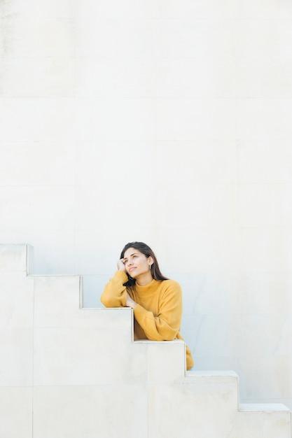 Donna premurosa che si leva in piedi contro la parete bianca Foto Gratuite