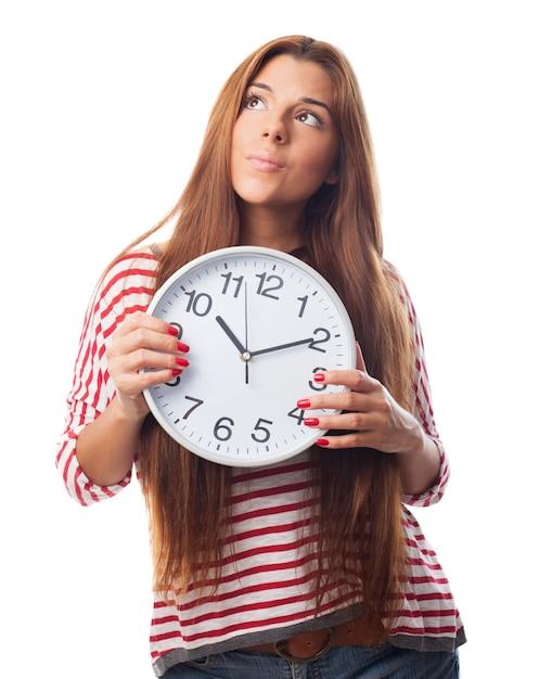 Donna premurosa che tiene un orologio Foto Gratuite