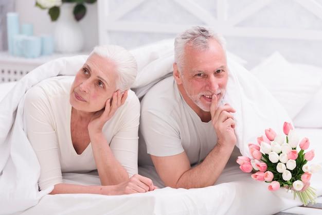 Donna premurosa senior che si trova sul letto accanto al suo marito che fa il mazzo del fiore del tulipano della tenuta di gesto di silenzio Foto Gratuite