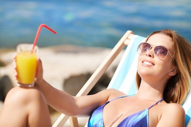donna preso il sole con un succo d'arancia Foto Gratuite