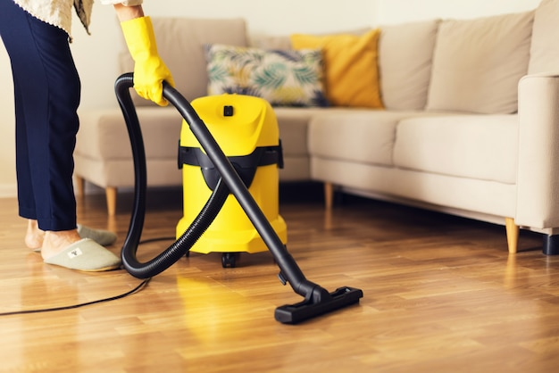 Donna pulizia divano con aspirapolvere giallo. copia spazio concetto di servizio di pulizia Foto Premium
