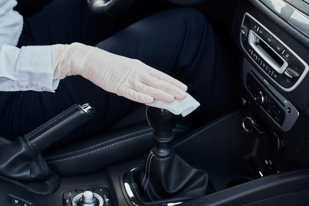 Donna pulizia interni auto. mano con detergente antibatterico per disinfettare la macchina Foto Premium