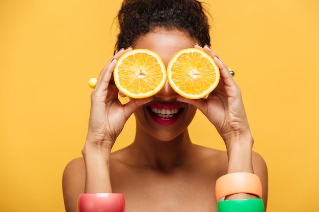 Donna razza mista divertente del primo piano con gli accessori di modo divertendosi e coprendo gli occhi di due metà dell'arancia isolata, sopra la parete gialla Foto Gratuite