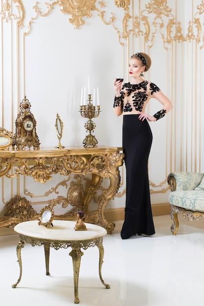 Donna reale bionda in piedi vicino al tavolo retrò in splendido abito di lusso con un bicchiere di vino in mano. interno. copia spazio Foto Premium