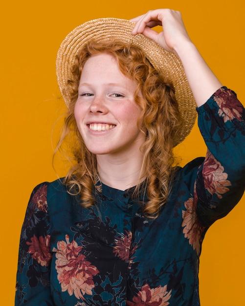 Donna riccia alla moda della testarossa in studio con fondo colorato Foto Gratuite