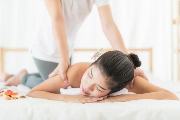 Donna rilassante mentre ricevendo il massaggio nella spa Foto Premium