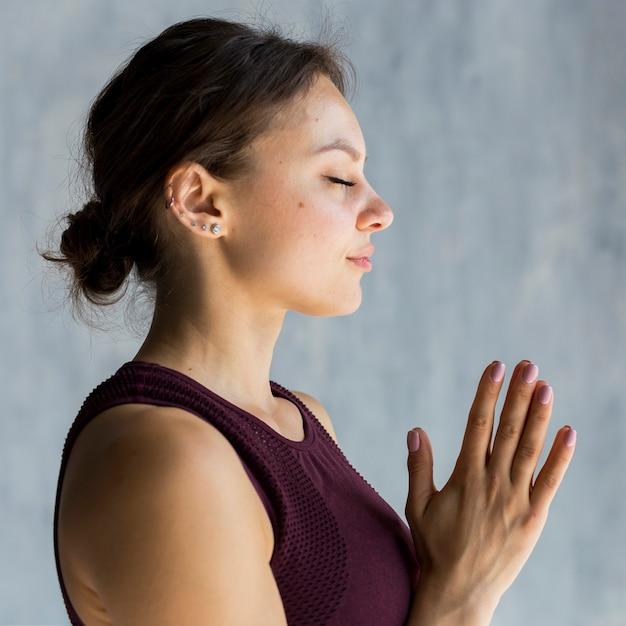 Donna rilassata che si tiene per mano in una posa di yoga del namaste Foto Gratuite