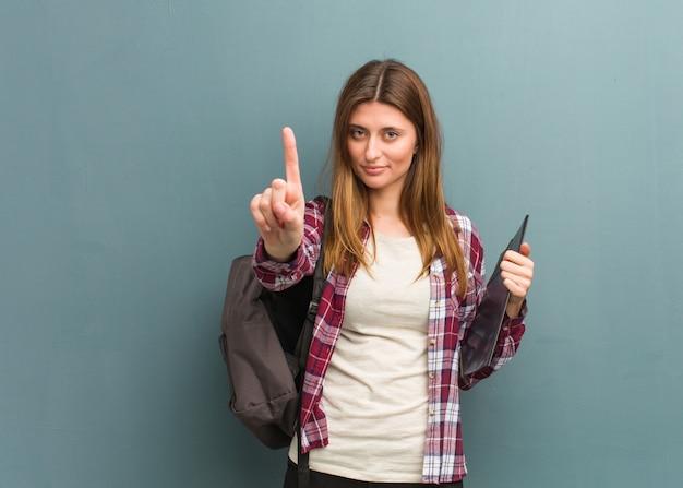 Donna russa del giovane studente che mostra numero uno Foto Premium