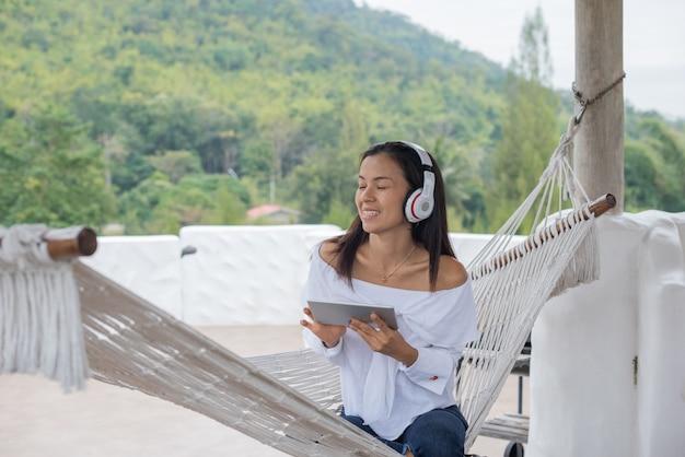 Donna sdraiata su un'amaca ascoltando musica con tavoletta Foto Gratuite