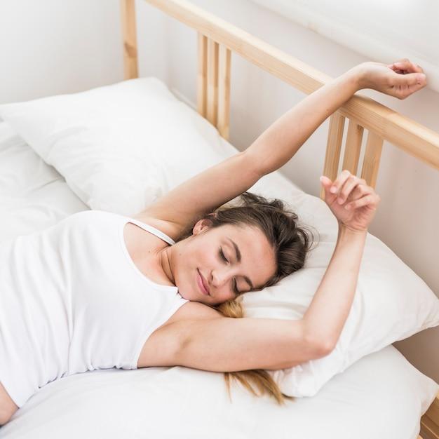 Donna sdraiata sul letto allungando le braccia Foto Gratuite