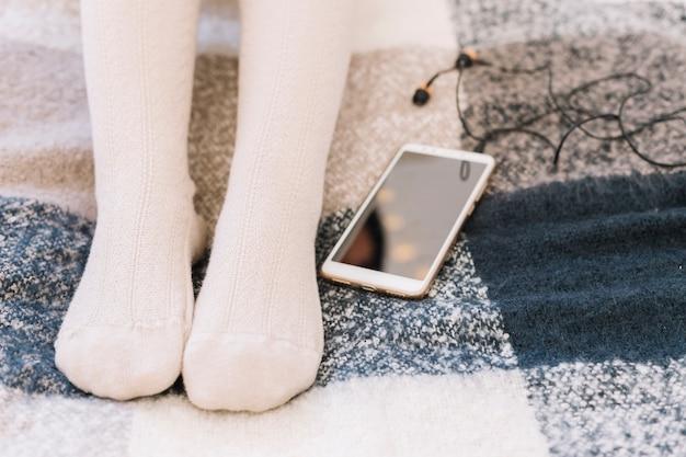 Donna sdraiata sul letto con lo smartphone Foto Gratuite