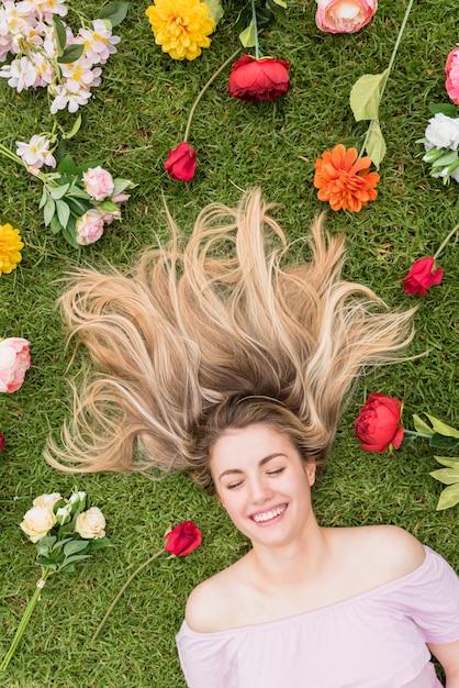 Donna sdraiata sull'erba con fiori diversi Foto Gratuite