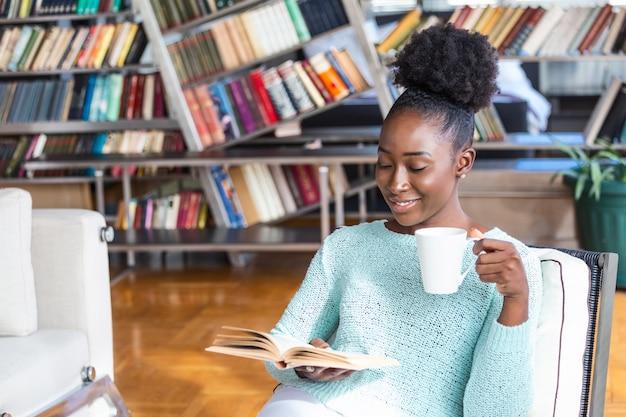 Donna seduta e bere caffè durante la lettura di un libro Foto Premium