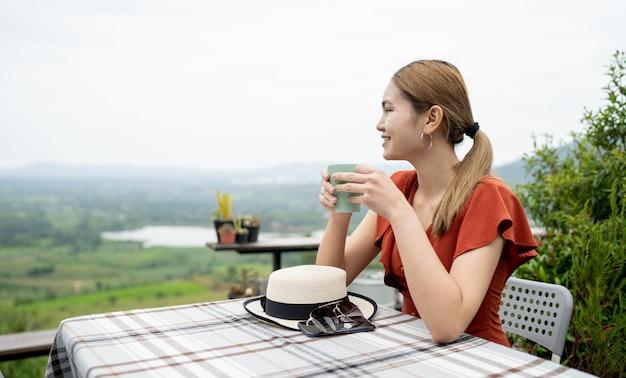 Donna seduta su un balcone con vista naturale Foto Premium