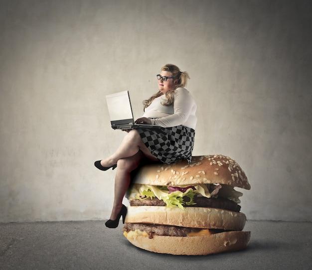 Donna seduta su un hamburger Foto Premium