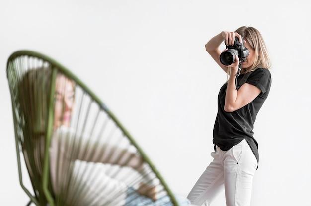 Donna seduta su una sedia e fotografata Foto Gratuite
