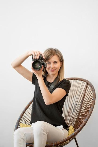 Donna seduta su una sedia e si prepara a scattare una foto Foto Gratuite