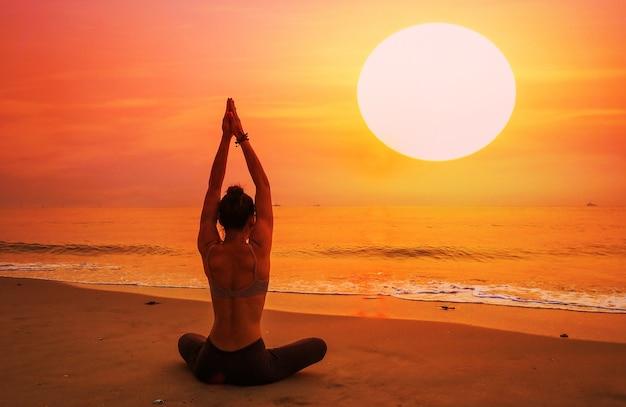 Donna seduta su una spiaggia con le braccia distese Foto Gratuite