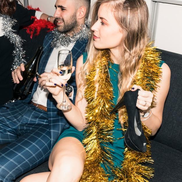 Donna seduta sul divano con un bicchiere di champagne Foto Gratuite