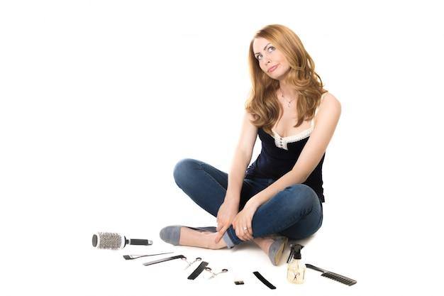 Donna seduta sul pavimento con gli strumenti barbieri Foto Gratuite