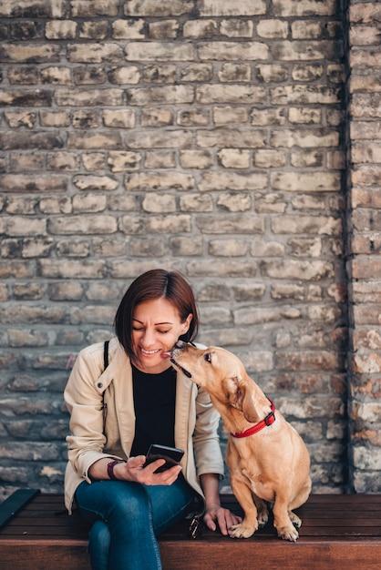 Donna seduta sulla panchina e usando il telefono mentre il cane si sta leccando il viso Foto Premium