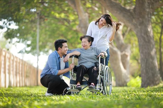 Donna senior asiatica che si siede sulla sedia a rotelle con il fronte felice di sorriso della famiglia sul parco verde Foto Premium