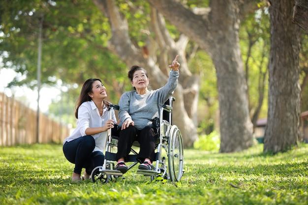 Donna senior asiatica che si siede sulla sedia a rotelle con il suo fronte felice di sorriso della sua famiglia del daugther sul parco verde Foto Premium