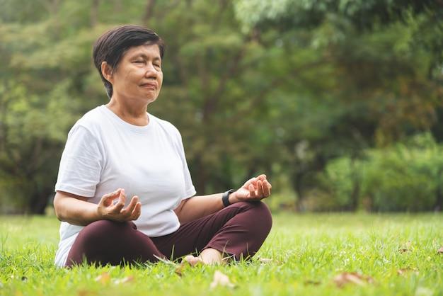 Donna senior asiatica nell'yoga di pratica della camicia bianca al parco. Foto Premium