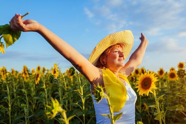 Donna senior che cammina nel giacimento di girasole di fioritura che si sente libero e che ammira vista. Foto Premium