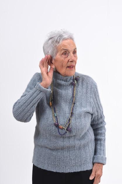 Donna senior che mette una mano sul suo orecchio perché non può sentire su fondo bianco Foto Premium
