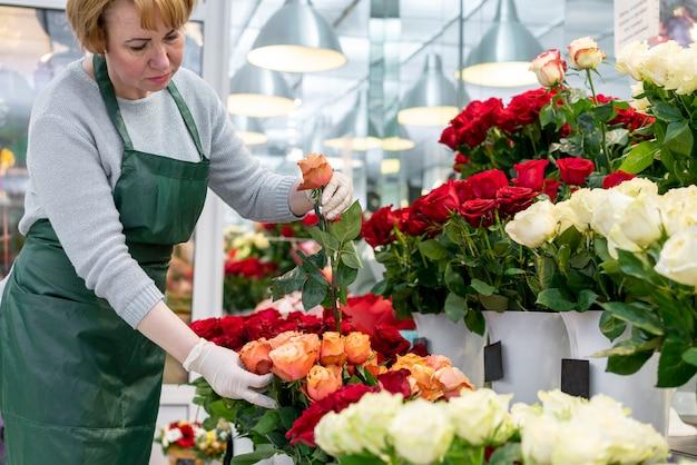 Donna senior che si occupa dei bei fiori Foto Gratuite